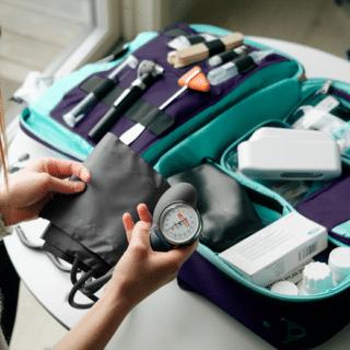 Legeutstyret i en legekoffert, utbrettet på et bord. Lege som holder blodtrykksmansjett i hånden. Blodprøver, sprøyter, undersøkelser, termometer, urinprøve vises i bakgrunnen