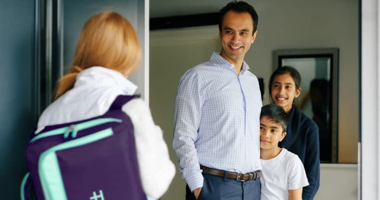 Lege med legekoffert står med ryggen til kamera og ringer på hjemme hos en familie / hos pasienten som venter på legen