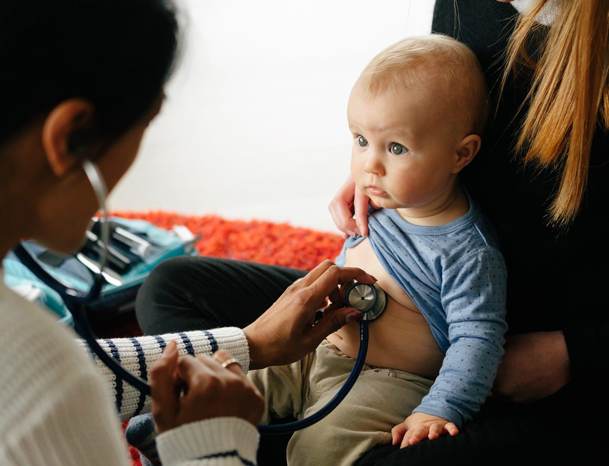 Lege undersøker barn på mors fang med stetoskop, på hjemmebesøk