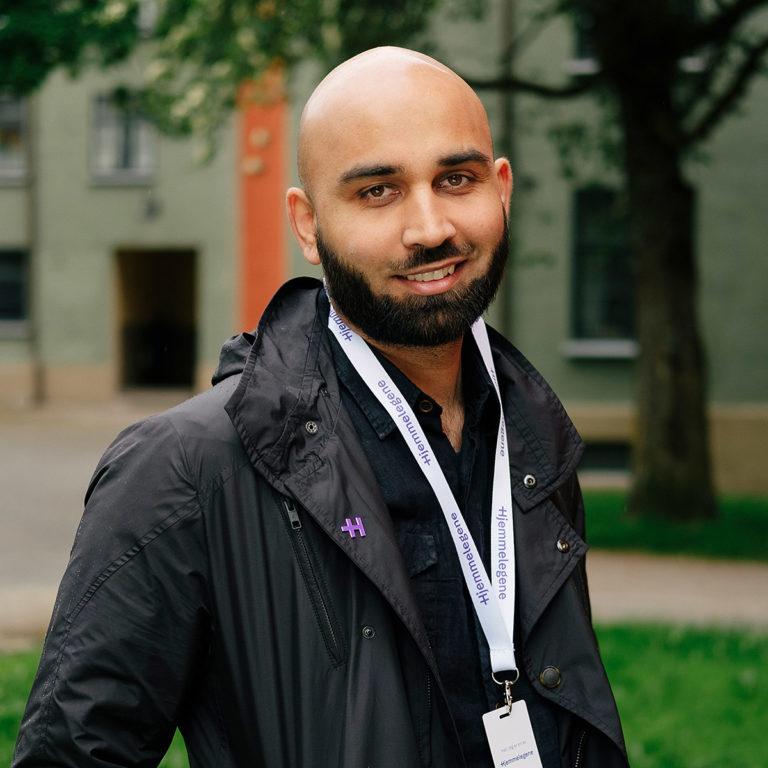 Lege Waleed står med Hjemmelegenes id-kort rundt halsen, smilende og klar for nye hjemmebesøk