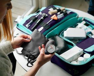 Lege med blodtrykksmåler og legebag, på hjemmebesøk