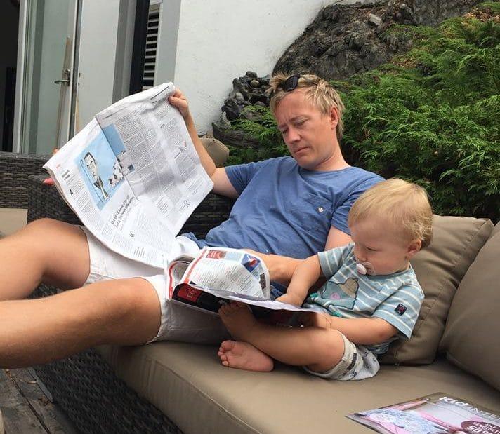 Lege hjem til far og barn som leser avisen på verandaen
