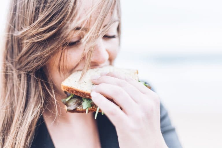 kvinne spiser sandwich