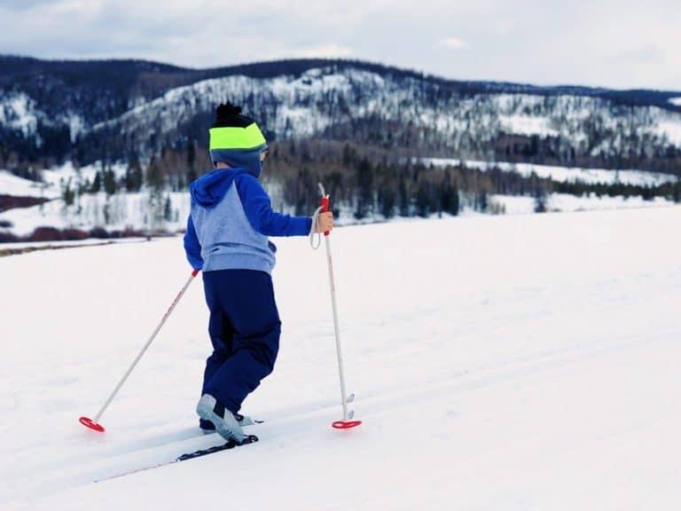gutt på ski over fjellet