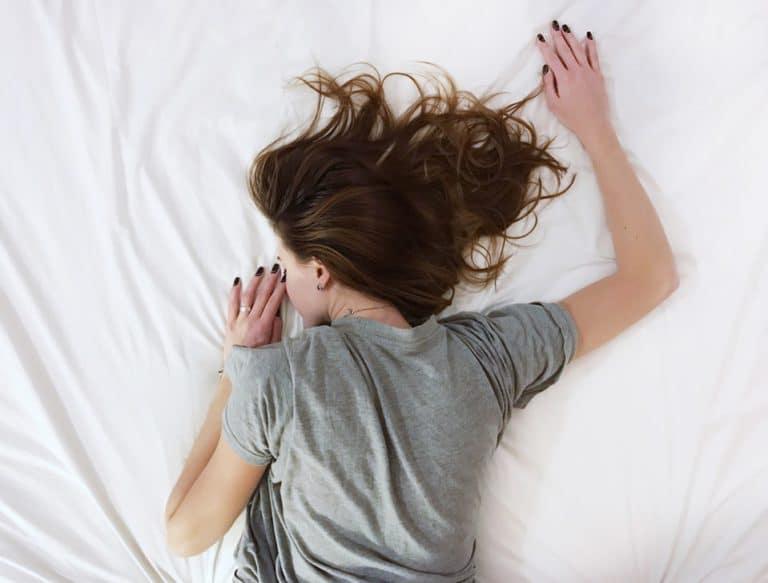 kvinne med angst depresjon ligger i sengen på magen